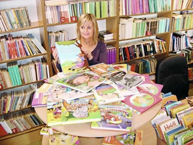 Anna Muszyńska z oddziału dla dzieci pokazuje książki kupione dzięki pomocy sponsora