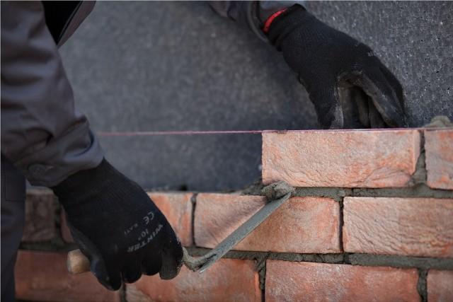 Murowanie ściany z użyciem kielniKielnia służy do nakładania zaprawy murarskiej, ale zbiera się nią także jej nadmiar.