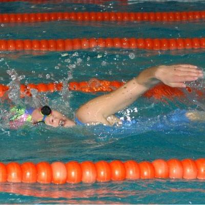 Młodzi pływacy w basenie czują się świetnie i szybko pokonują kolejne metry dystansu