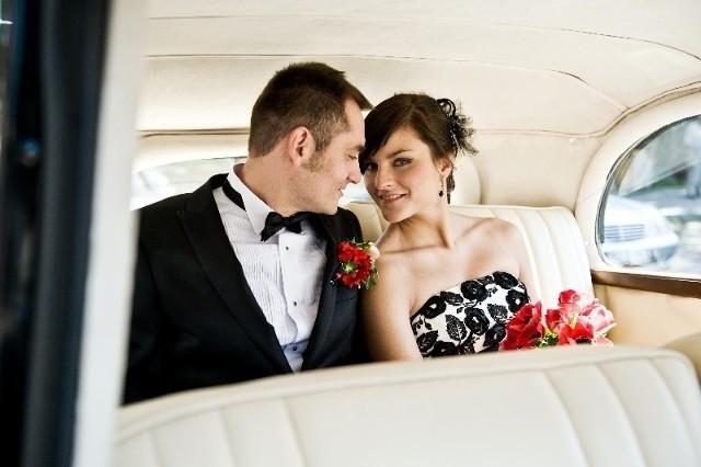 Stylizacja panny młodej – biel połączona z czernią i czerwienią – jest obecna w dekoracji stołu i auta.