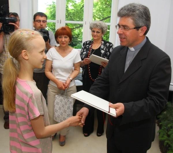Agata Brzozowska na swoim plakacie umieściła duże serce, do którego wpadają ofiarowane złotówki. Gratulacje za zwycięstwo w konkursie złożył jej m.in. ks. Marian Niemiec.