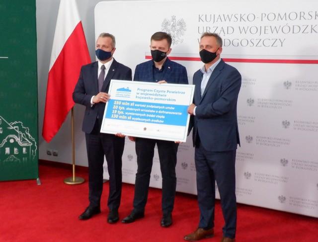Stojący od lewej: wojewoda Mikołaj Bogdanowicz, minister Łukasz Scheiber i prezes WFOŚiGW w Toruniu Ireneusz Stachowiak prezentują na planszy główne efekty programu Czyste Powietrze w regionie.