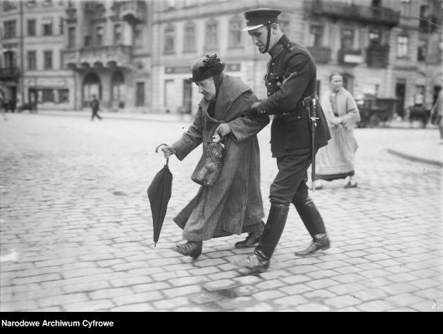 Policjant przeprowadzający staruszkę przez ulicęNa zdjęciu: policjant przeprowadzający staruszkę na drugą stronę Krakowskiego Przedmieścia w Warszawie. W tle widać plac Zamkowy, a w głębi - ulicę Podwale i kamienicę Dziewulskich.1925 rok.