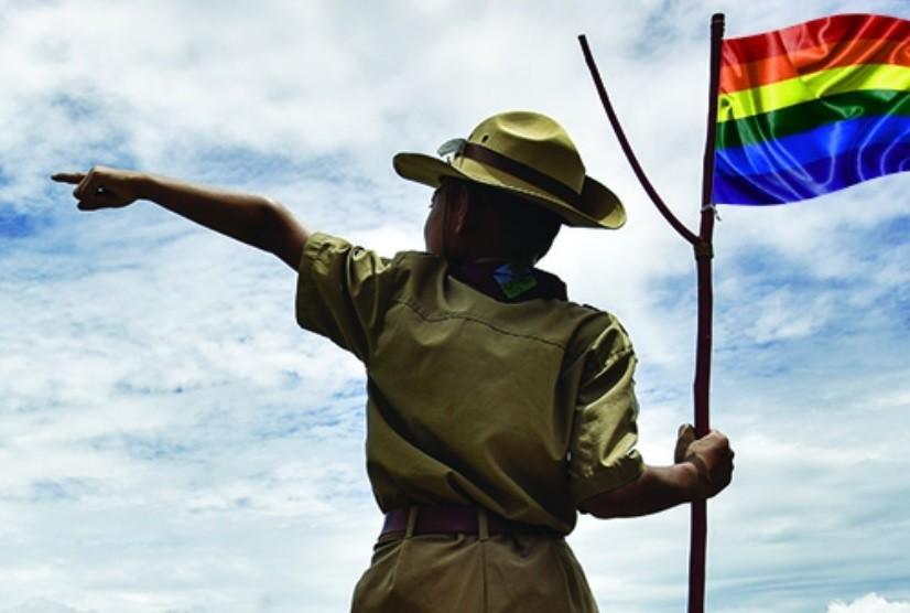 Chłopiec w harcerskim mundurze i z flagą ruchu LGBT wita...
