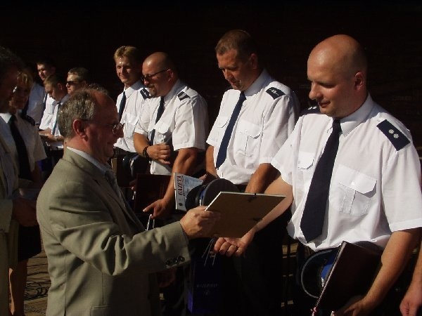 Podkomisarz Artur Krajewski (pierwszy z prawej)  odbiera pamiątkowy dyplom i gratulacje.