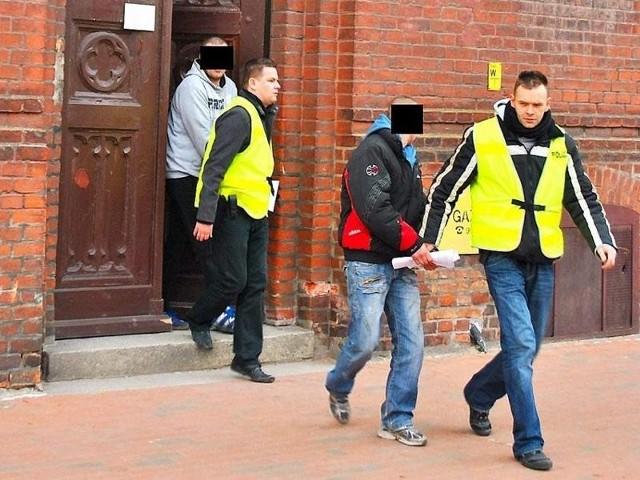 Policjanci wyprowadzają aresztowanych z sądu
