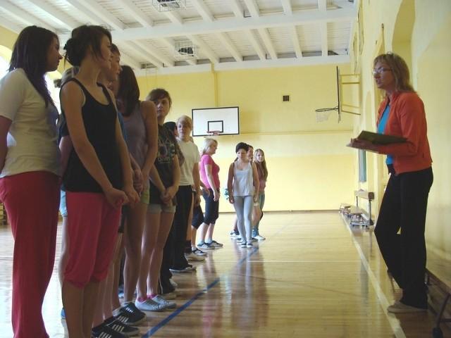 Dziewczyny z technikum spedycyjnego z nauczycielką Romualdą Kudłą przygotowują się do zajęć na połówce sali gimnastycznej. Na drugiej będą ćwiczyć chłopcy.