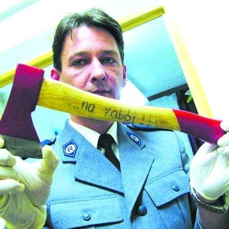 """Dariusz Kędzior, oficer prasowy białostockiej policji, pokazuje siekierę, którą Tomasz L. dostał od swojej dziewczyny. Był na niej napis: """"Kocham Cię... na zabój!!!"""" (zdjęcie z 2006 r.)"""