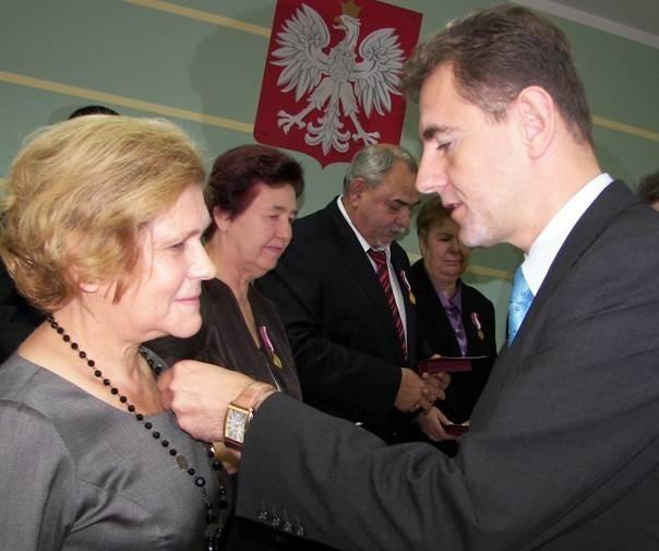 Złoty medal za długoletnią służbę z rąk wojewody podlaskiego Macieja Żywno przyjmuje Anna Ziniewicz dyrektor Domu Dziecka w Krasnem
