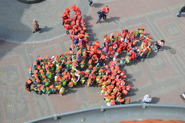 """W środę, 8 maja, o godz. 11.00 pod pomnikiem Bachusa w Zielonej Górze, dzieci z miejskich przedszkoli utworzyły """"żywy krzyż"""". Pomysłodawcą inicjatywy jest Polski Czerwony Krzyż, którzy w ten sposób chciał uczcić Światowy Dzień Czerwonego Krzyża oraz Czerwonego Półksiężyca. - Myślę, że taki happening to świetny pomysł, aby uczcić to święto. Bardzo mnie cieszy, że nasza inicjatywa spotkała się z takim odzewem wśród najmłodszych zielonogórzan. No i ważne, że pogoda dopisała – twierdzi Marcin Bleszcz z PCK. PRZECZYTAJ TAKŻE: W Zielonej Górze powstaje pomnik Czesława Niemena. Za prace odpowiada Artur WochniakW akcji wzięły udział m.in. przedszkola nr 17, 6, 46 i 34. Aby wpasować się happening dzieci trzymały w górze czerwone kartki, część była również ubrana w tym kolorze. Na przedszkolaków czekały na miejscu także dodatkowe atrakcje, odbywały się gry i zabawy, a nawet malowanie twarzy. - Podobna akcje mają dzisiaj miejsce w wielu miastach w Polsce, m.in. w Warszawie, a w Lubuskiem na przykład w Nowej Soli czy Żaganiu. Warto przypomnieć, że w 2019 roku Polski Czerwony Krzyż obchodzi stuletnią rocznicę powstania – informuje M. Bleszcz. – Już teraz chciałbym wszystkich zaprosić na naszą następną imprezę. 23 maja w Zielonej Górze zorganizujemy zbiórkę krwi. Na uczestników czekają konkursy, a dla dawców upominki czy vouchery.Czy zielonogórski PCK zamierza w przyszłości powtórzyć happening. – Nie wykluczamy tego, to był nasz pierwszy raz, ale może warto powtórzyć to również za rok – uważa Marcin Bleszcz. Polecamy wideo: Żacy z Uniwersytetu Zielonogórskiego będą bić rekord Guinessa w bocci"""