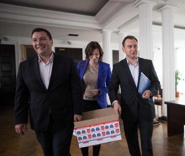 Piotr Bors i Tomasz Trela niosą karton z prawie 20 tys. podpisów pod projektem uchwały przeciwko podwyżkom.