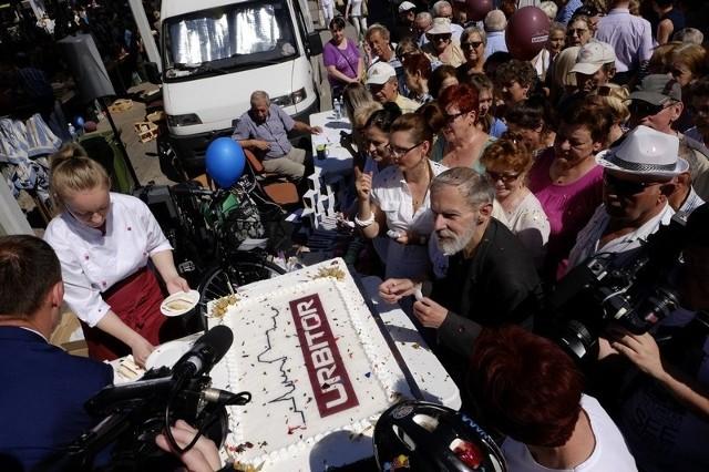 """Modernizacja """"zieleniaka"""" na targowisku miejskim przy Szosie Chełmińskiej w Toruniu trwała ponad pół roku (od października 2017 roku do maja 2018 roku). Dziś (8 czerwca) oficjalnie otwarto zmodernizowaną część targowiska. Podczas oficjalnego otwarcia był tort dla gości, loteria fantowa, kiermasz regionalnych wyrobów. Była także okazja, by wykonań badania profilaktyczne. Inwestycja kosztowała około 3,2 mln zł, ich wykonawcą była firma Girder z Włocławka.Rynek przy Szosie Chełmińskiej to największe targowisko w Toruniu i regionie. Jego atutem jest położenie w centrum miasta. Czynne jest od poniedziałku do soboty w godzinach 6-18 oraz w niedziele w godz. 6-14, także w niedziele bez handlu. Zieleniak, który przeszedł modernizację, to najbardziej na północ wysunięta część targowiska, gdzie handluje się głównie owocami i warzywami. W efekcie nad zieleniakiem pojawiło się nowe modułowe zadaszenie. Wcześniej wykonano nową nawierzchnię placu z kostki betonowej i płyt chodnikowych oraz instalacje podziemne, które zapewniły poprawę komfortu handlu. Ponadto cały sektor wyposażono w nowe stoły do handlu. Zamontowano oświetlenie, które pozwala na robienie zakupów także w pochmurne i deszczowe dni oraz popołudniami. Pod wiatami wprowadzono zakaz palenia papierosów."""