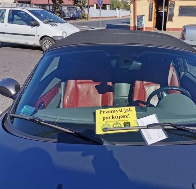 """Na pierwszych, źle zaparkowanych samochodach w Przemyślu pojawiły się żółte kartki akcji """"Przemyśl jak parkujesz""""."""