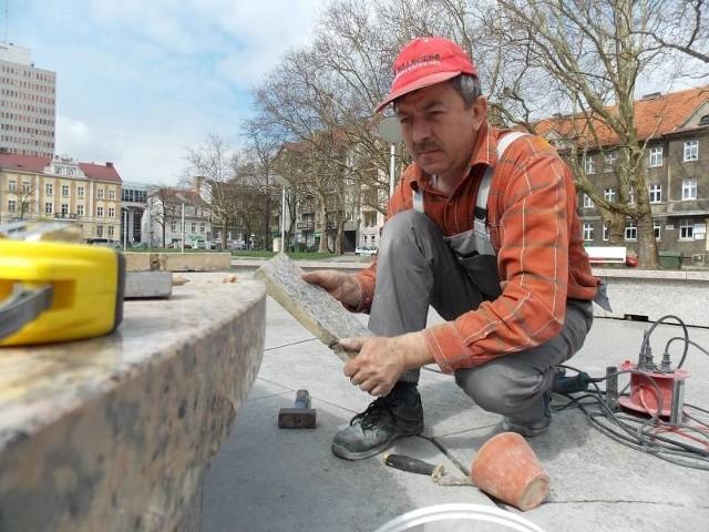 Ostatnie poprawki przed sezonem: Zdzisław Chowański naprawia nieckę fontanny na placu Grunwaldzkim