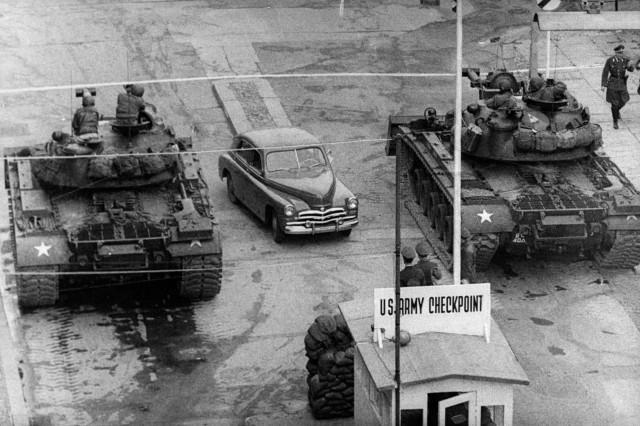 """Berlin, październik 1961 r. Samochód przejeżdżający między amerykańskimi czołgami na punkcie granicznym """"Charlie"""", Checkpoint Charlie, dziś miejsce chętnie odwiedzane przez turystów."""