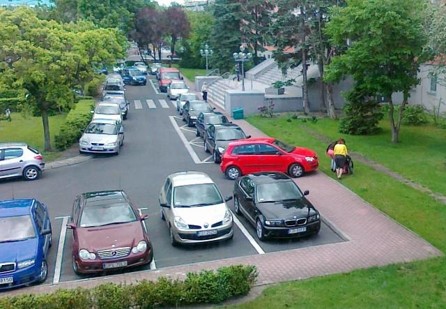 Postronne osoby pomagają niepełnosprawnemu ominąć auto, które zastawia chodnik.