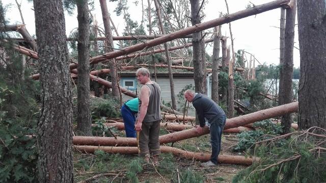 """Gwałtowna burza z silnym wiatrem wyrządziła także straszne szkody na terenie ośrodka wypoczynkowego Dal-Sol koło Parchowa. Drzewa przygniotły samochody i spadały na domki letniskowe. Trwa sprzątanie terenu i liczenie strat. W całej gminie Parchowo ludzie nie mają wody i prądu, zasięgu telefonii komórkowej. Niektóre miejscowości są dosłownie """"odcięte od świata"""". Oglądaj także: Usuwanie zniszczeń po nocnej nawałnicy w powiecie bytowski"""