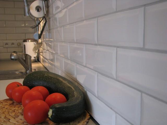 Kafle na ścianie w kuchniBiałe kafle są ponadczasowe. Płytki widoczne na zdjęciu mają nietypowy rozmiar i kształt, który pięknie załamuje światło.