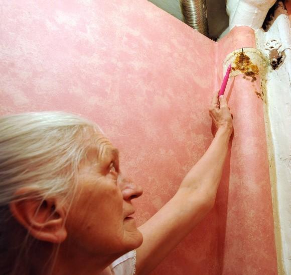 Krystyna Grabowicz pokazuje nam, gdzie mimo malowania rury i próby zaklejenia szczeliny domowym sposobem, fekalia nadal wydobywają się na zewnątrz.