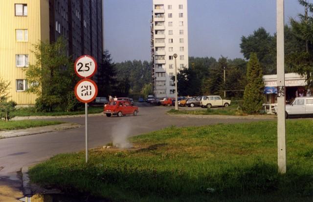 """Tak jeszcze kilkadziesiąt lat temu wyglądał krajobraz osiedla Bieżanów. Przed blokami parkowały fiaty 126p i trabanty, a mieszkańcy robili zakupy głównie w osiedlowych sklepikach, nazywanych """"drewniakiami"""" lub """"blaszakami""""."""