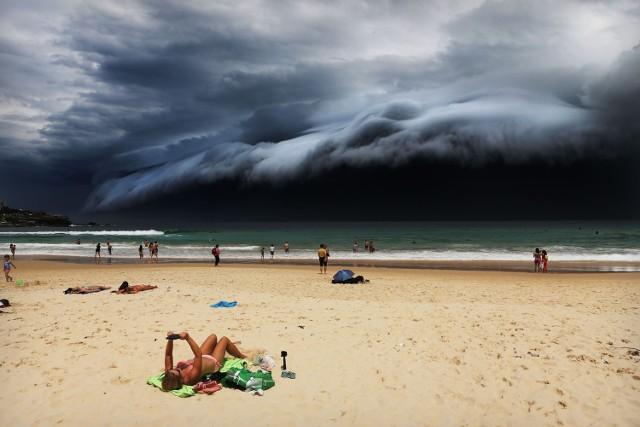 """Fotografia nagrodzona pierwszym miejscem w kategorii """"Przyroda"""" na tegorocznym konkursie World Press Photo. Widzimy kobietę  na plaży w Sydney, która nie zwraca uwagi na nadciągające """"chmury tsunami"""""""