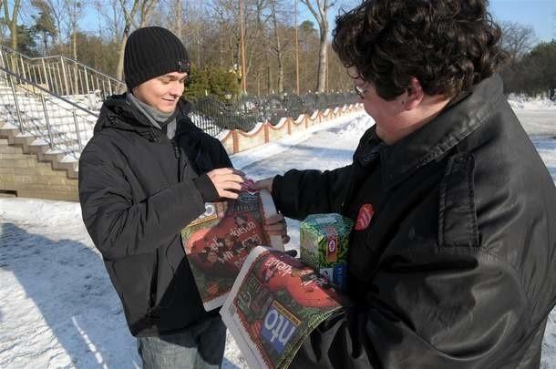 Bartosz Więckowski wrzuca pieniądze do puszki wolontariusza Mateusza Kriegera.