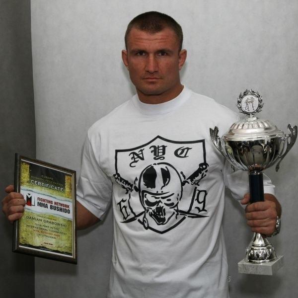 Damian Grabowski z pucharem i dyplomem wywalczonymi na Litwie.