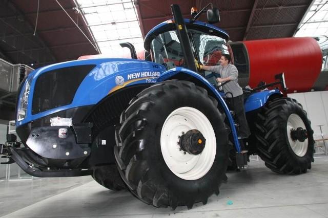 Pracownik firmy New Holland czyści ogromny ciągnik rolniczy przed prezentacja na wystawie AGROTECH, która w tym roku będzie rekordowo duża.