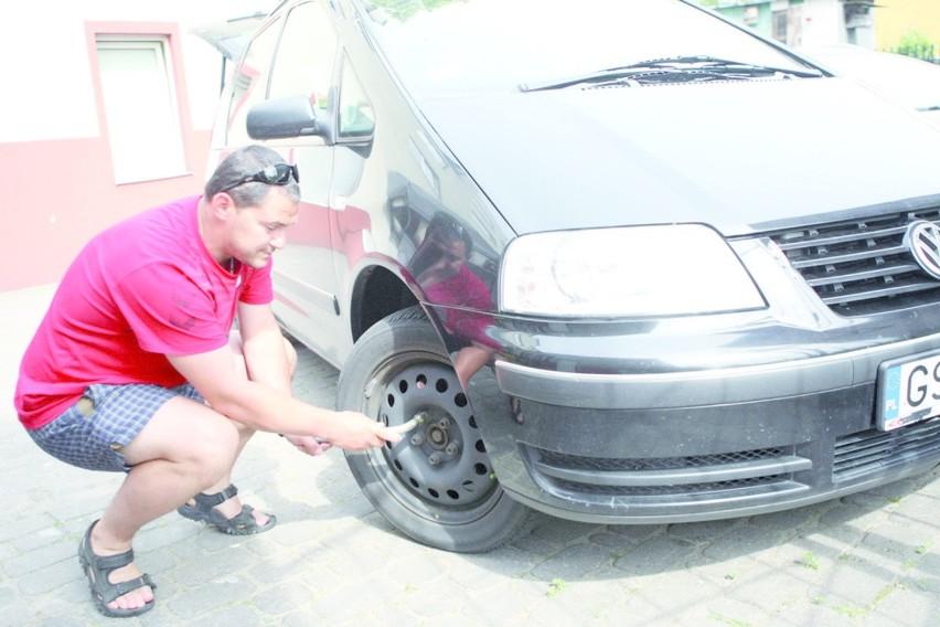 Tomasz Rybak przy samochodzie ze zniszczonymi felgami.