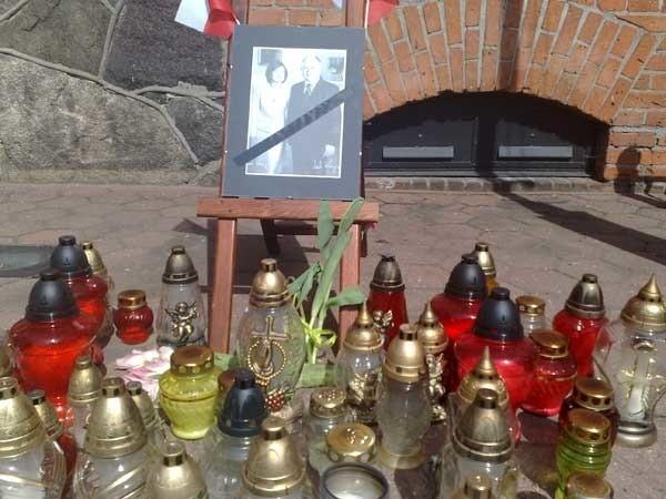 Przed szczecineckim ratuszem ktoś ustawił zdjęcie Lecha Kaczyńskiego i jego żony Marii, a wokół mieszkańcy zapalają znicze.