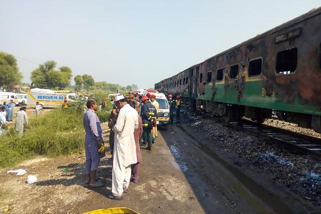 Ratownicy obok spalonego wagonu pociągu w pobliżu Rahim Yar Khan w Pakistanie