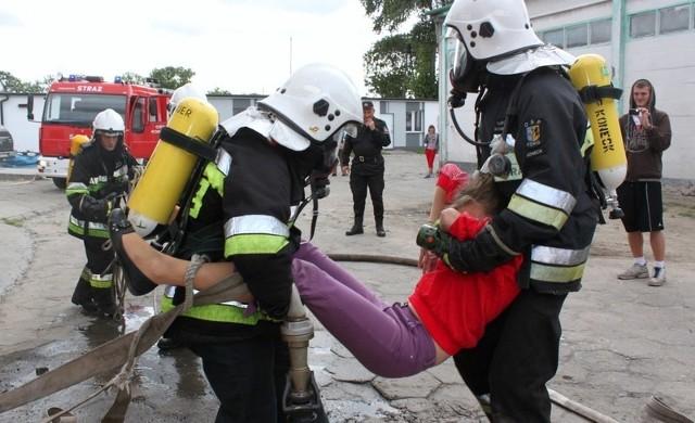 """Strażacy wynoszą nieprzytomną ofiarę z """"zadymionego i płonącego"""" pomieszczenia."""