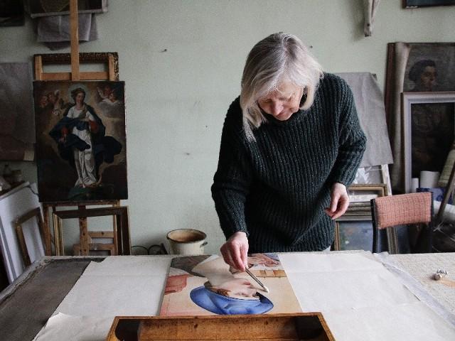 """Wiktoria Tołłoczko-Tur przeprowadza konserwację """"Portretu żony z obrączką"""". Teraz nie ma na nim śladów kitów, które zostały nałożone podczas wcześniejszej konserwacji ani mechanicznych uszkodzeń."""