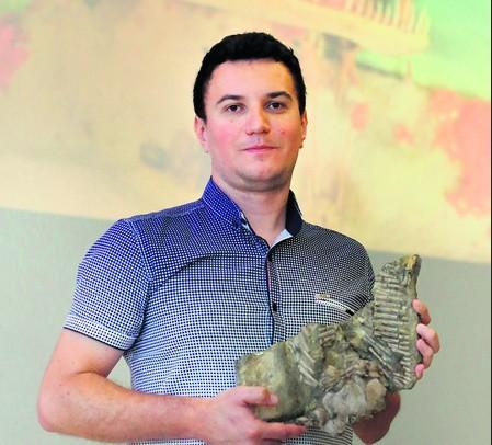Dawid Surmik z fragmentem szkieletu odnalezionego proneustikozaura śląskiego