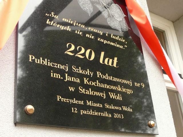 Tablica jubileuszowa na ścianie szkoły.