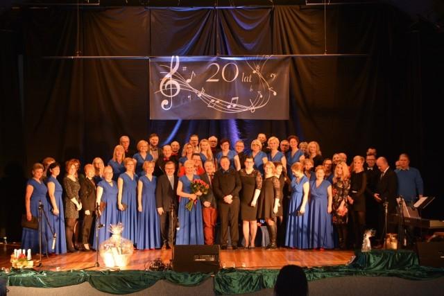 """Tęsknota grupy mogilnian do wspólnego śpiewania zaowocowała w 1998 r. powstaniem """"Chóru Dorosłych"""". Próby zespołu rozpoczęły się w listopadzie, a pierwszy jego występ zorganizowano już 3 stycznia 1999 r. Jesienią 2000 r. chór przyjął plebiscytowe miano Ewy Paluch """"Hemantus"""". W tym samym czasie mogileńscy chórzyści otrzymali ujednolicone stroje, a na nowe Tysiąclecie ich artystyczny dorobek zaprezentowany został na własnej płycie. Dwanaście lat później """"Hemantus"""" wzbogacił się o drugą płytę. W jego dorobku są liczne koncerty na miejscu, a także udziały w przeglądach i festiwalach w kraju i poza jego granicami.  Skupiający dziś 28 osób """"Hemantus"""", działający przy  Mogileńskim Domu Kultury koncertował m. in. w Londynie, a w minionym roku w Lloret de Mar i barcelońskiej katedrze. Współzałożycielami """"Hemantusa"""" byli Sławomir Paluch i Włodzimierz Dobersztyn - jego pierwszy prezes, którego pamięć uczczono minutą ciszy. W jego zespole znaleźli się wówczas również: Alina Dobersztyn, Wioletta Stojek, Elżbieta Rólska, Anna Sosnowska, Ewa Paluch, Iwona Waszak, Jacek Kurant, Andrzej Stojek i Krzysztof Grzelczak. Okazały jubileusz 20-lecia """"Hemantusa"""", który obchodzono  w sali mogileńskiego kina """"Wawrzyn"""", urozmaicony okolicznościową wystawą, zgromadził liczne grono sympatyków i wielbicieli zespołu wielce zasłużonego  w artystycznej promocji Mogilna. Słowa uznania i gratulacje jubilatowi przekazali: starosta mogileński Bartosz Nowacki i jego zastępca Marian Mikołajczak, przewodniczący Rady Powiatu Robert Musidłowski, burmistrz Leszek Duszyński, przewodniczący Rady Miejskiej Paweł Molenda, prezes Mogileńskiego Towarzystwa Kultury Teresa Kujawa oraz Dyrektor Mogileńskiego Domu Kultury Jan Szymański. Uczestnicy jubileuszowej uroczystości mogli wysłuchać występu zespołu - jubilata, a  uświetniły ją także   zaprzyjaźnione chóry """"ProNobis"""" z  Janikowa pod dyrekcją Sławomira Palucha i """"Harmonia"""" ze Strzelna pod dyrekcją   Eweliny Boesche Kopczyńskiej. Obecnie swój kunszt w """"Hemantusie"""" """