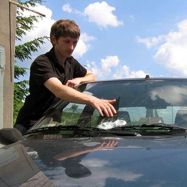 Mateusz Jurek pokazuje rozbitą szybę w swoim peugeocie. Widać wyraźnie dwa ślady od uderzeń kamieni