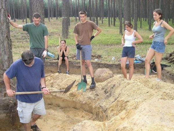 Profesor archeologii Uniwersytetu Łódzkiego  obrysowywuje studentom ślady pochówku w  grobie jednego z Gotów.