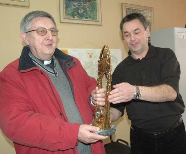 Tadeusz Peterman, naczelnik sekcji kryminalnej w Nysie przekazuje odzyskany relikwiarz proboszczowi Mikołajowi Mrozowi.
