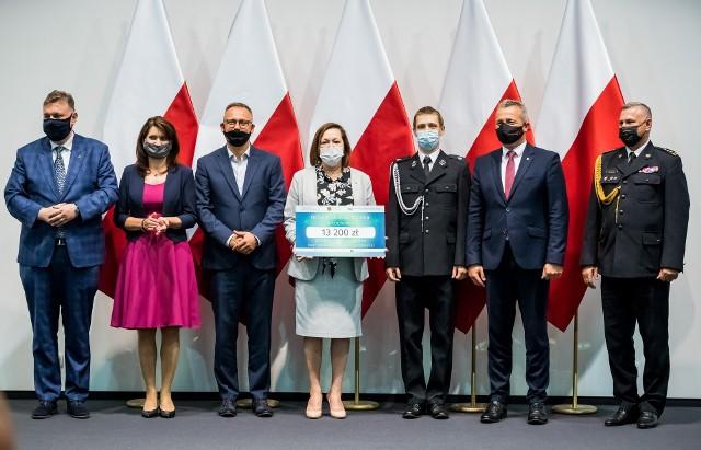 Uroczysty moment przekazania vouchera dla OSP Łochowo przedstawicielom gminy Białe Błota