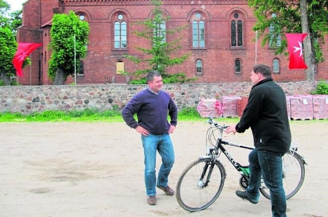 Maciej Mostowy i ks. Dariusz Leman (z rowerem) na placu, gdzie powstanie nowy zbór.  W tle, pod murem, widoczne palety z dachówkami