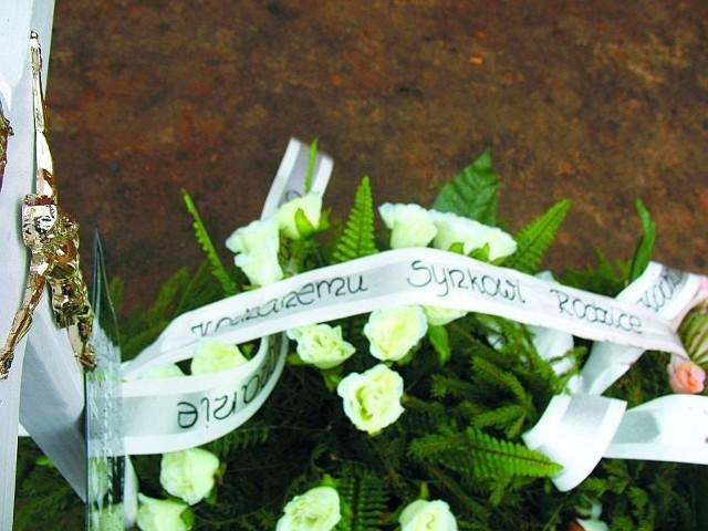 """Maluśki biały grób. Białe kwiaty. I biała szarfa: """"Kochanemu synkowi rodzice""""."""