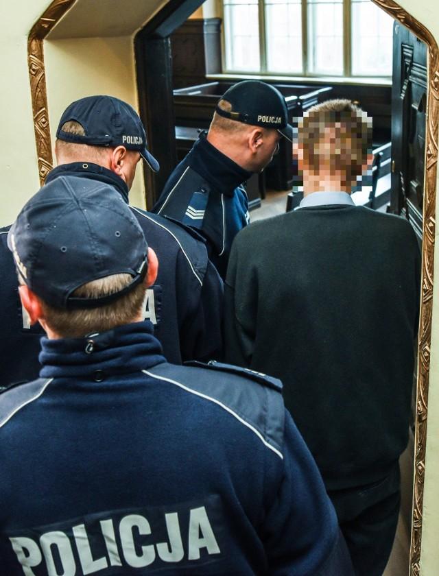 Żaden z oskarżonych, ani Maciej K. (na zdj. prowadzony przez policję na salę rozpraw), ani Sławomir G. nie przyznają się do winy.