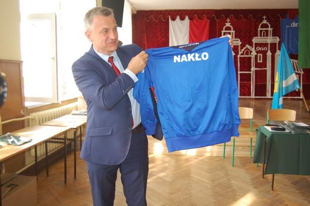 Sławomir Napierała, burmistrz Nakła, prezentuje dresy, w których wystąpią podczas igrzysk w Chełmnie sportowcy z gminy Nakło. Ufundował je samorząd