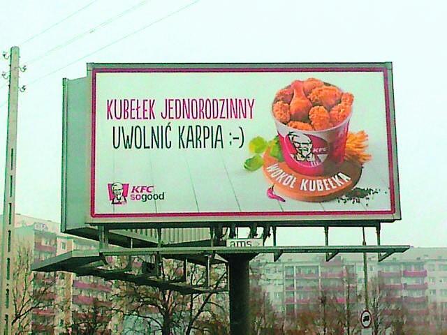 """Kubełek KFC. Pan Karp chce uwolnić kurczaki :-)Na billboardzie KFC napisano: """"Kubełek jednorodzinny. Uwolnić karpia :-)"""""""