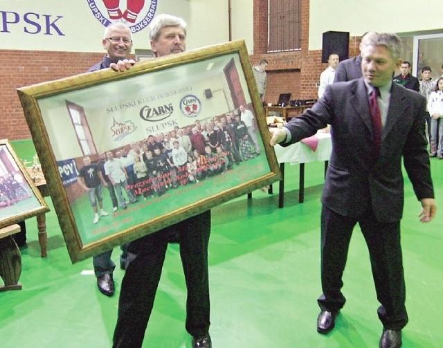 Kazimierz Adach (z prawej) przekazuje prezent dla przedstawiciela urzędu miasta.