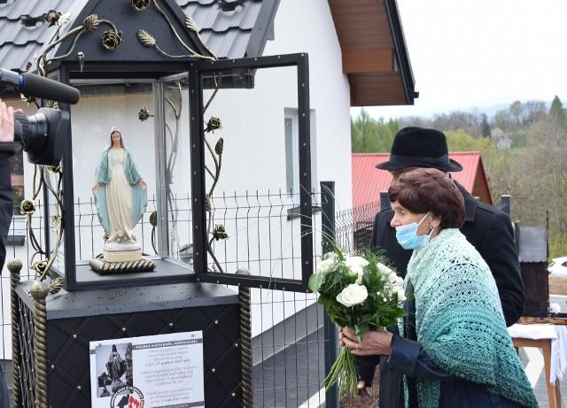 Teresa Młynarczyk przy swoim domu i kapliczce, w której umieszczono ocalałą z pożaru figurkę Matki Bożej Niepokalanej