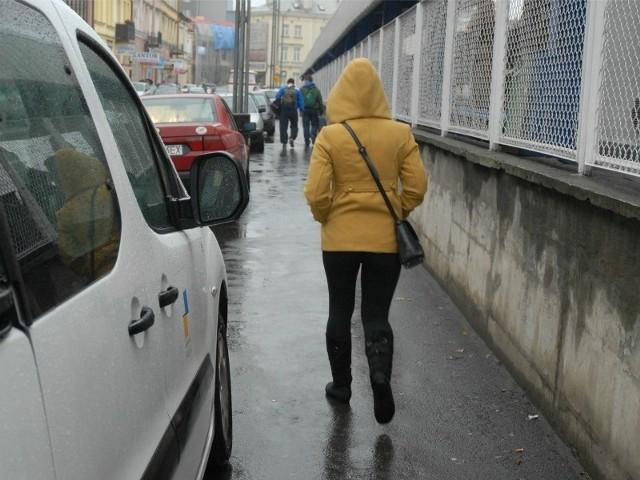 """Samochody utrudniają przejście pieszym i niszczą chodnik. Odkąd zaczęły tu parkować, na starym asfalcie utworzyły się koleiny. Stoi w nich woda, a piesi depczą po plamach oleju. Wczoraj kierowcy byli bardziej """"uprzejmi"""" i stawali na chodniku tylko dwoma kołami. Ale za to utrudniali ruch na jezdni."""