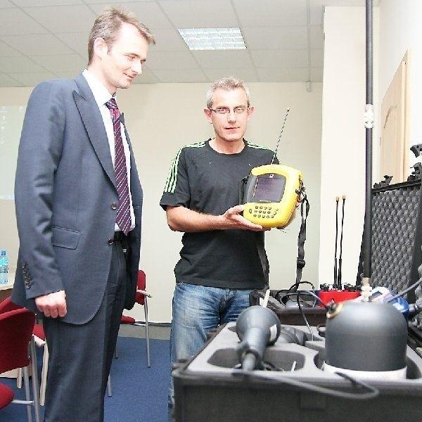 Roland Urbański z MPEC prezentuje  urządzenie do wykrywania nieszczelności  na podstawie szumu wycieku. Obok prezes  Michał Pietraszewski.