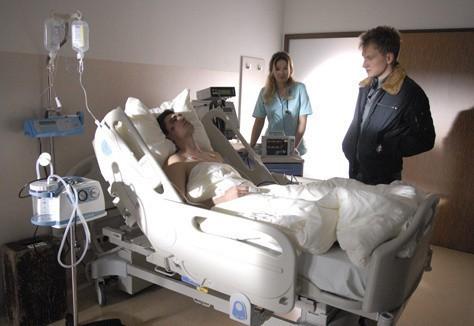 Komisarz Bromski przesłuchuje ofiarę wypadku motocyklowego. Nad bezpieczeństwem pacjenta czuwa lekarka (w tej roli Marta Dąbrowska).